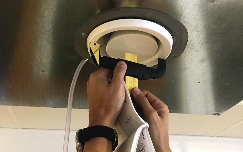 två händer som som håller i ett justeringsverktyg för ventilation