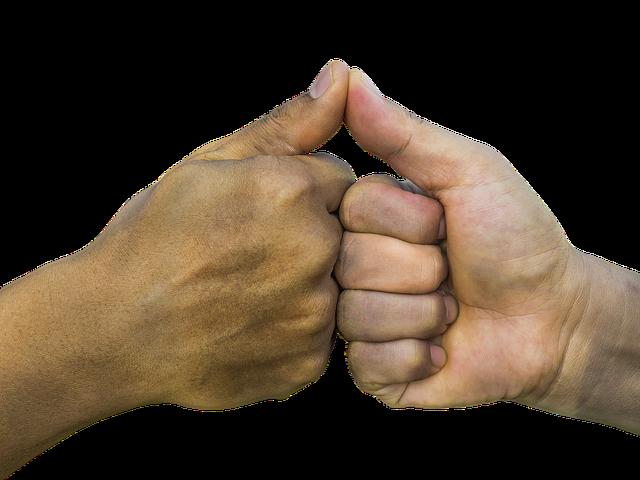 två knytna händer med tummarna uppe som nuddar varandra